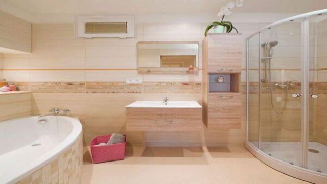 Moderní koupelnu velegantní béžové ozvláštňuje osvětlená nika